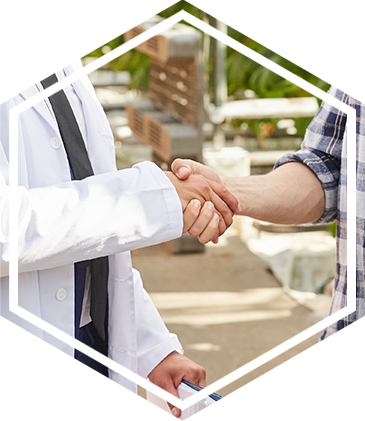 A man and a person in a doctor's coat shake hands outside